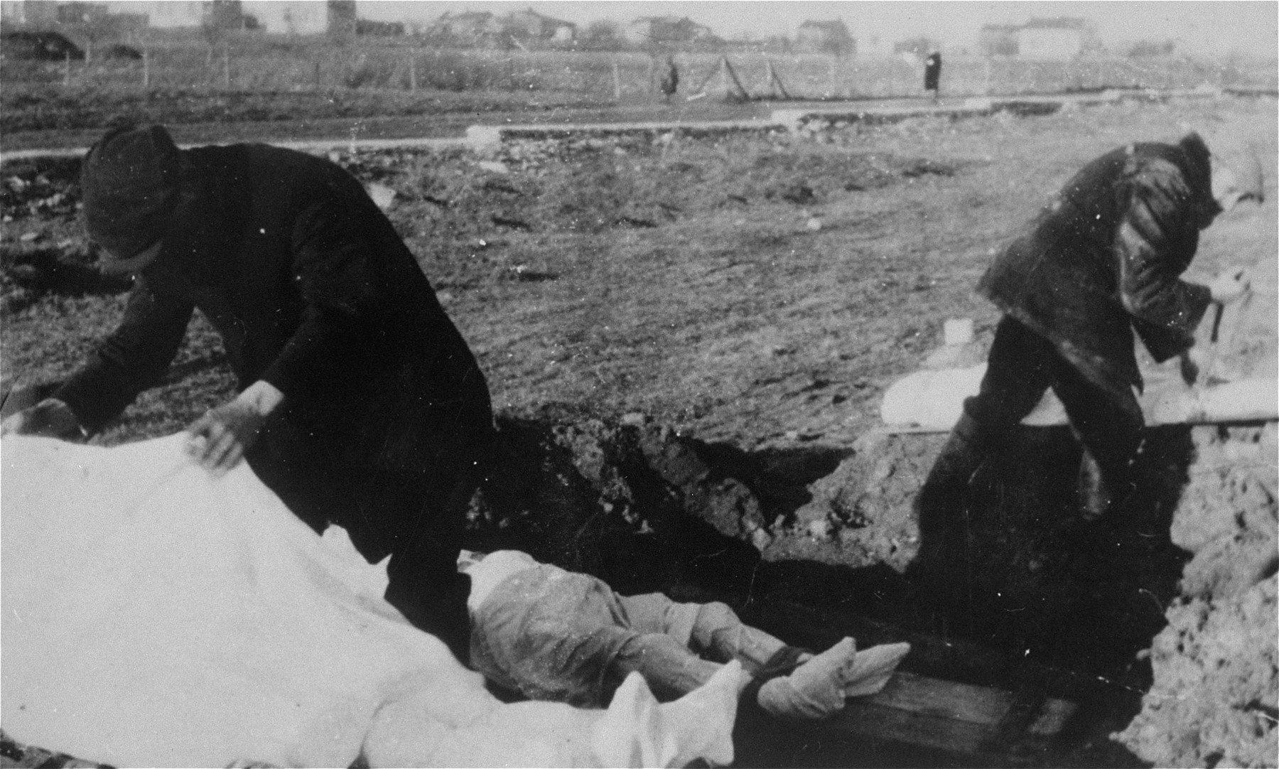 Two men prepare bodies for burial at the Jewish cemetery in Kutno.