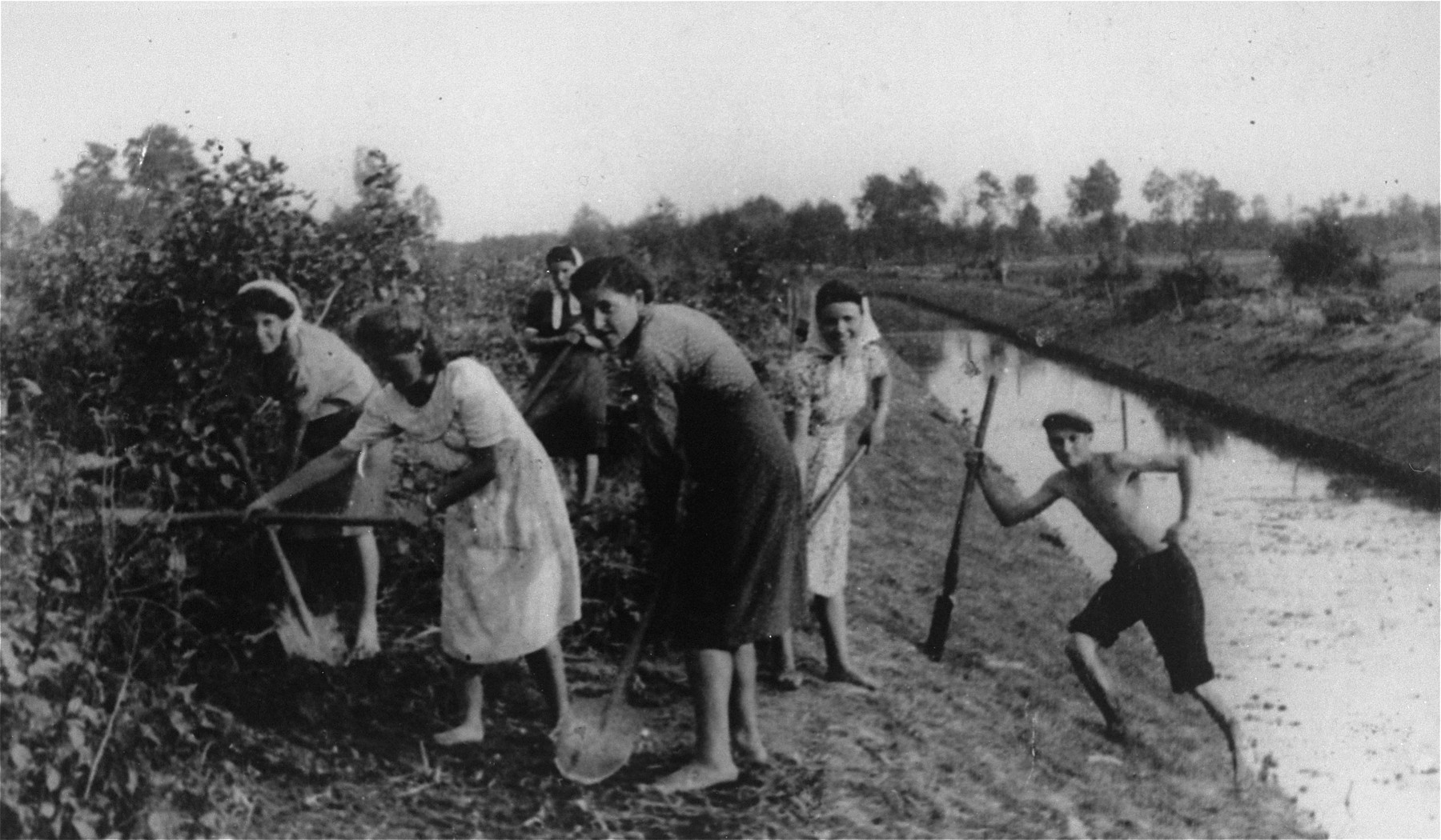 Jews from the Kozienice ghetto at forced labor digging alongside a canal in the nearby village of Wolka.  They are working for the Gorczycki firm who was building a canal.  From left to right are Wasserman, Salka Bendler, Anka Mandelbaum, Sabina Goldstein and Bezalel Berneman.
