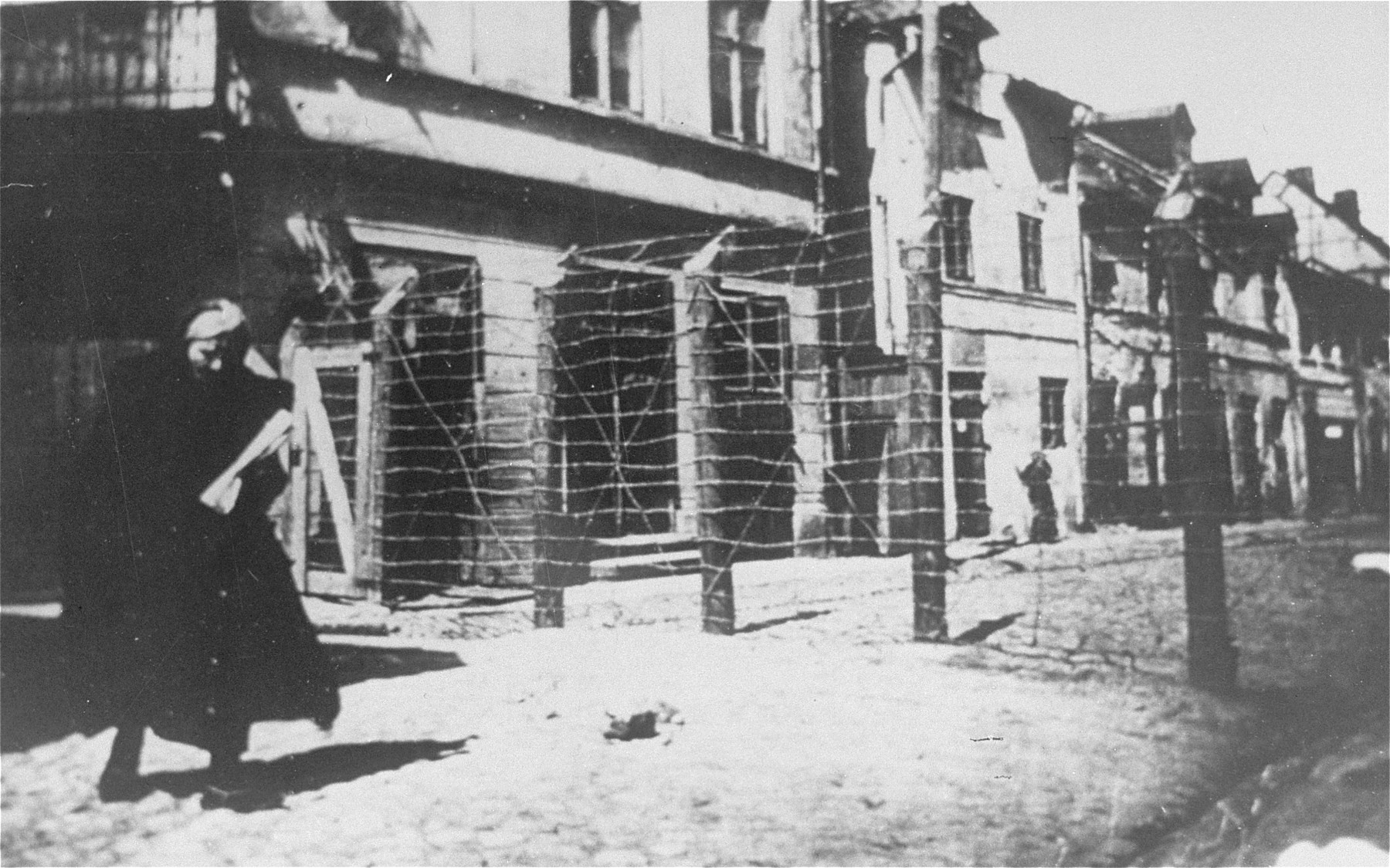 View of the gate and barbed wire fence at the entrance to the Leczyca ghetto.