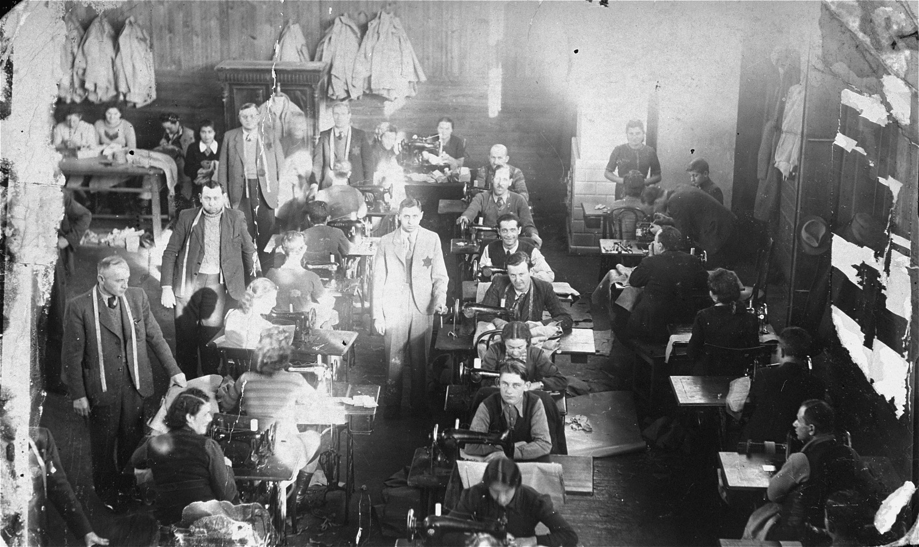 Jews at forced labor sewing military uniforms for the German army and air force at a factory in the Olkusz ghetto.  Among those pictured are the tailor Gliksztajn (standing on the left, with a measuring tape around his neck), Salka Szwarcberg (sitting next to Gliksztajn at one of the sewing machines), Chana Zuckerman (seated third from the front, in the middle row),  and Wof Cygler (later Walter Ziegler, seated at the back on the far right).