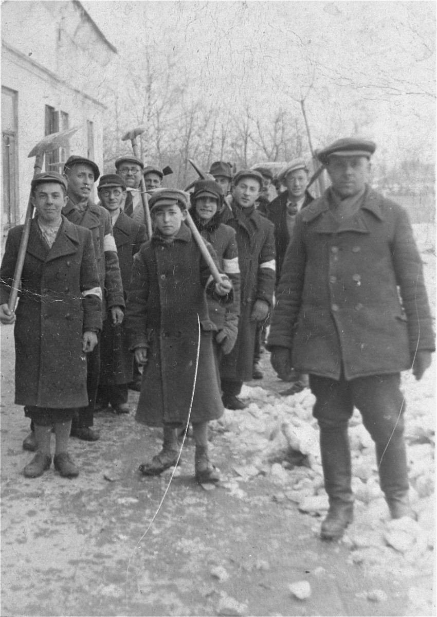 Escorted by a Pole, a group of Jewish men and youth from Olkusz march to a work site carrying shovels.    Among those pictured is the donor's brother, who was 12 years old at the time (front row, center).
