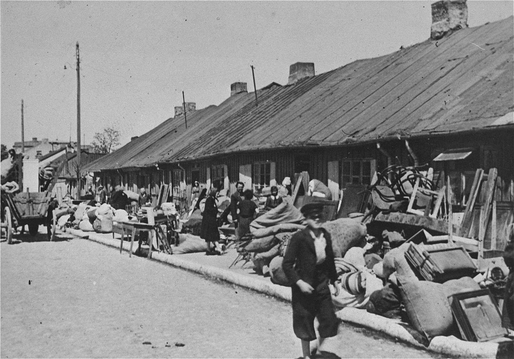 Piles of furniture and household belongings of Jews who are being transferred to the ghetto cover the pavement of a street in Kutno.