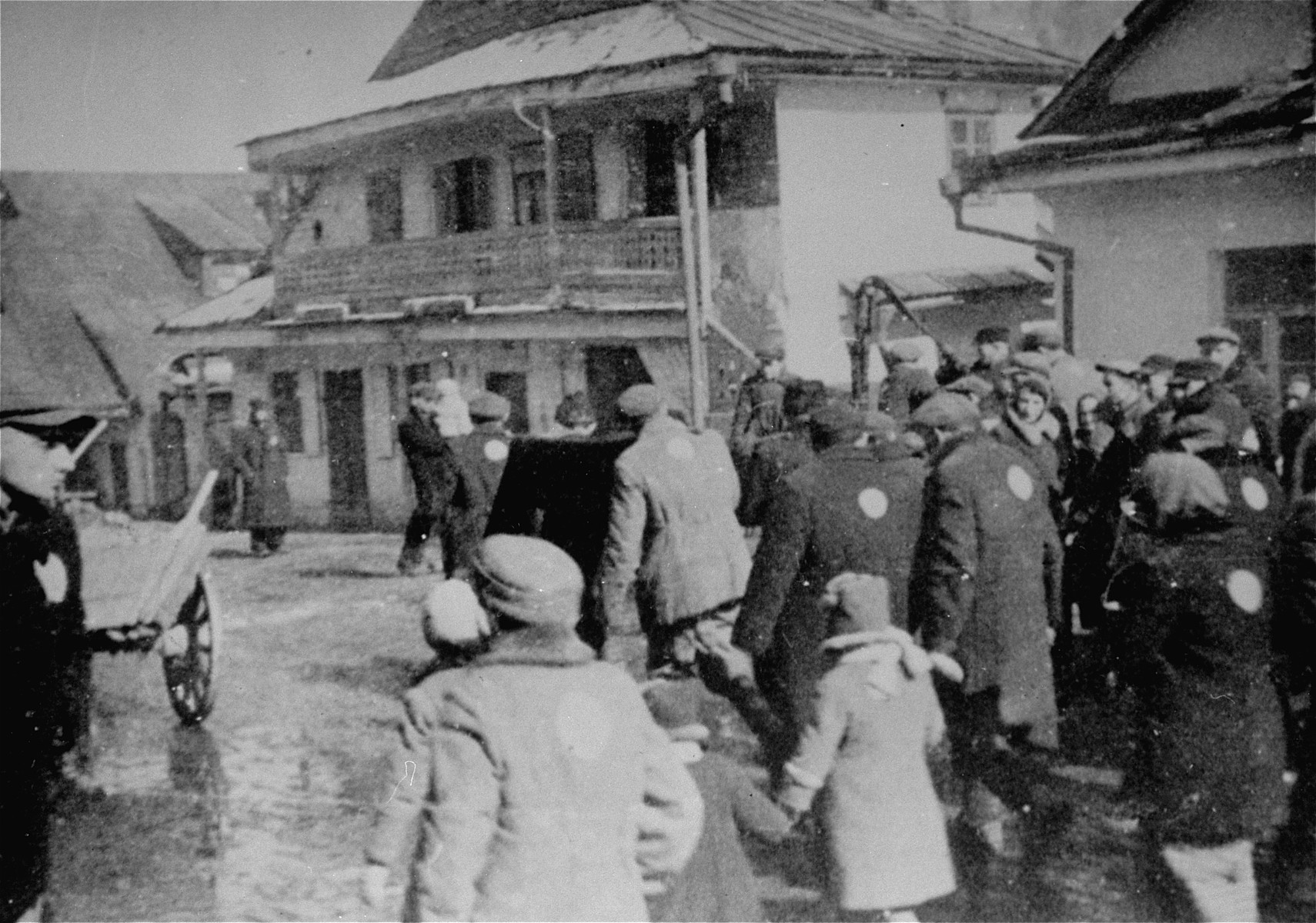 Jews wearing circular badges walk through town during a deportation action from the Krzemieniec ghetto.
