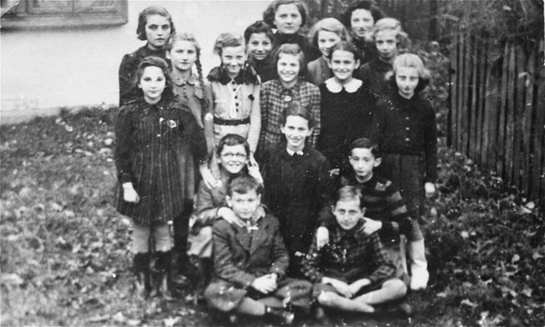 Group portrait of pupils attending a clandestine school in the Mielec ghetto.  Among those pictured are Irene Geminder (second row from the top, second from the right) and Toska Spyrina (kneeling between two boys in the second row).  The teacher stands in the top row, center.