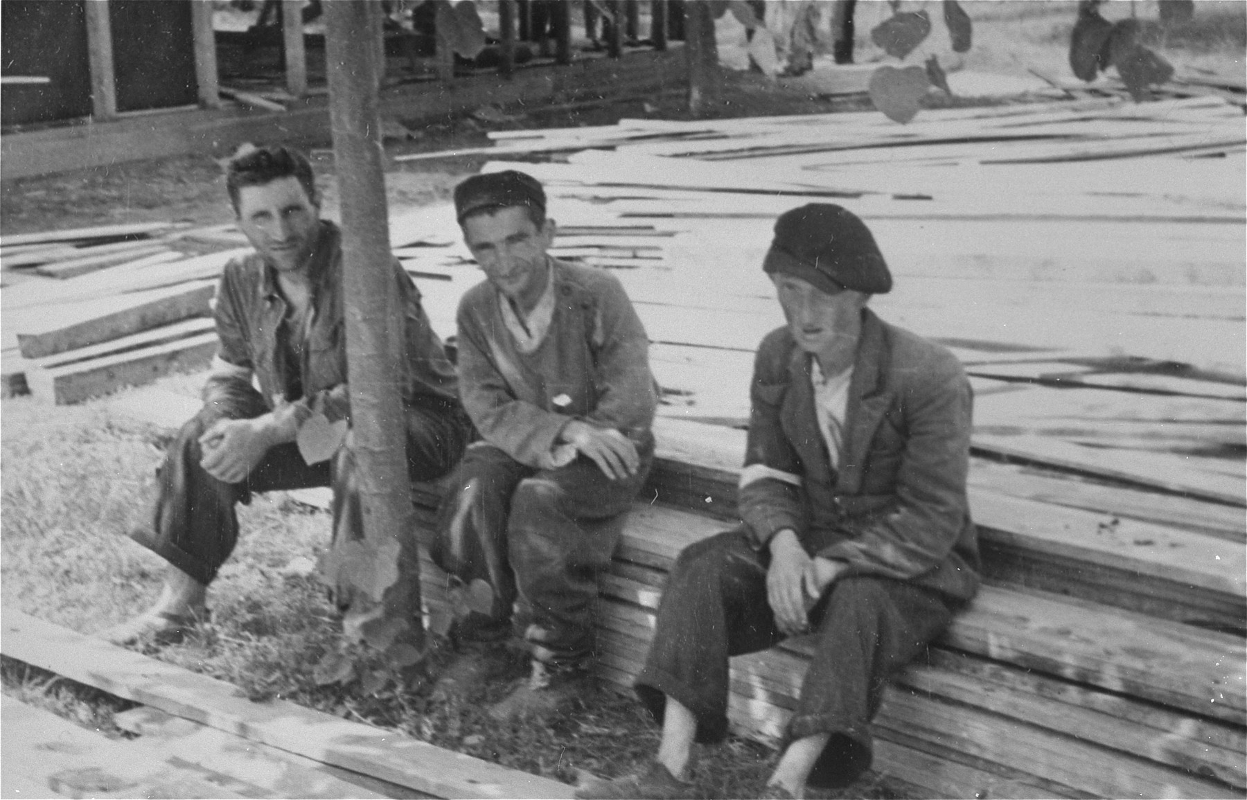 Three Jewish men who have been conscripted for forced labor, sit on a pile of lumber in Konskowola.