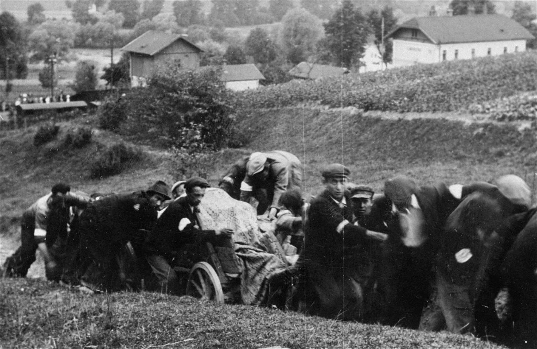 The bodies of sixty Jews from Limanowa who were executed in the Jewish cemetery, are moved to a burial site.  A group of Jewish men wearing armbands pulls a wagon loaded with the corpses along an unpaved path.