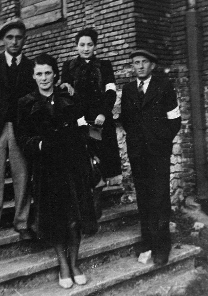 Four young Jewish men and women pose wearing armbands on a staircase in the Olkusz ghetto.  Among those pictured are the donor, Rose Grinbaum and her cousin.