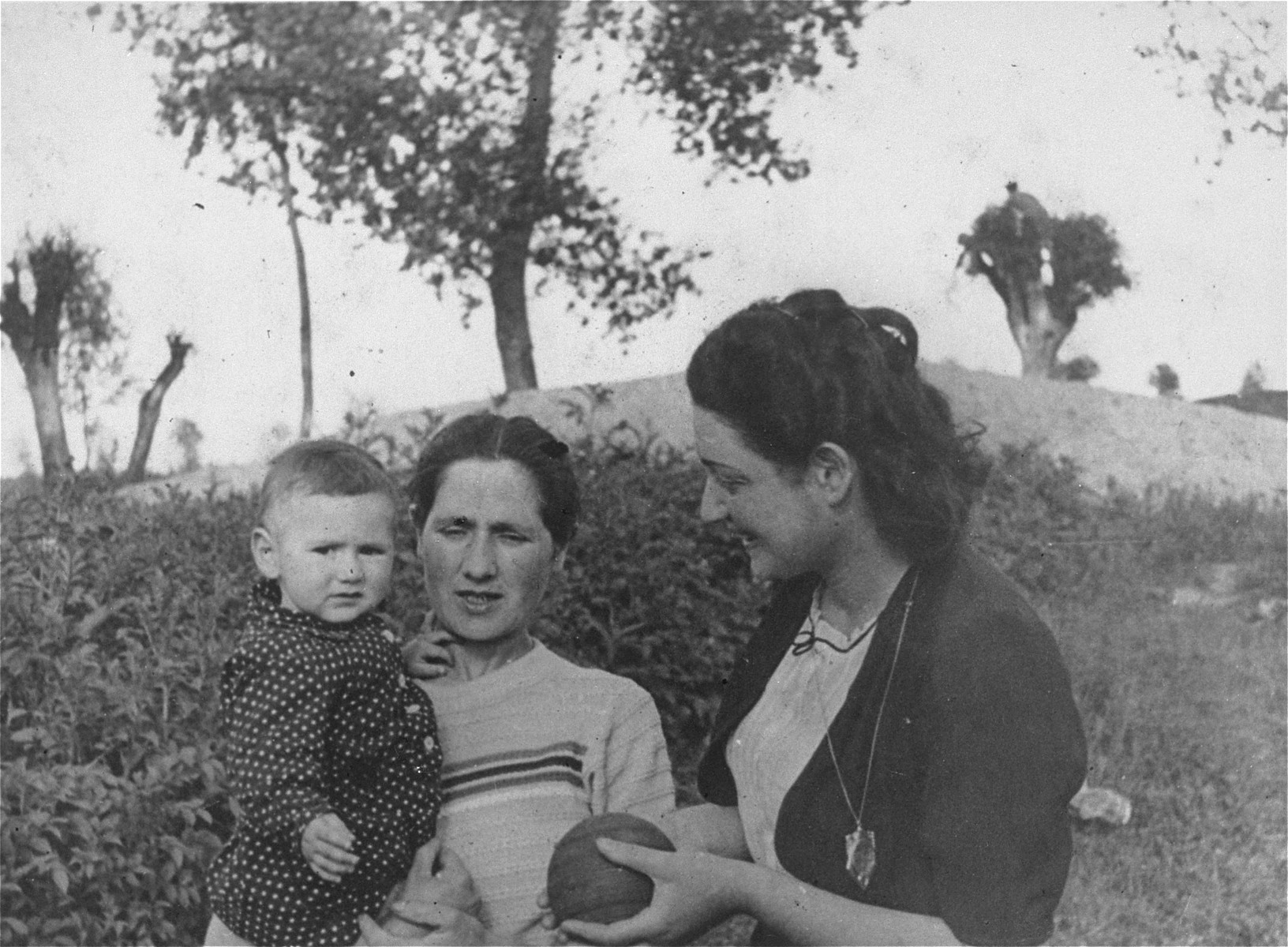 A young Jewish mother poses with her child and niece outside in a field.  Pictured from right to left are: Sabina Weinstock, her aunt, Hinda Eidenberg and Hinda's child. Hinda and her child later perished in the Trawniki concentration camp.