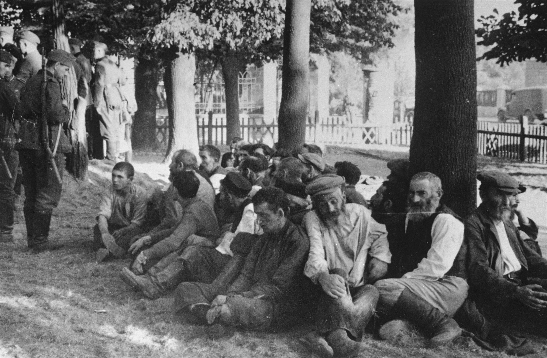 Jews rounded-up in Konskie wait for orders to participate in the digging of a grave for the bodies of four German soldiers.