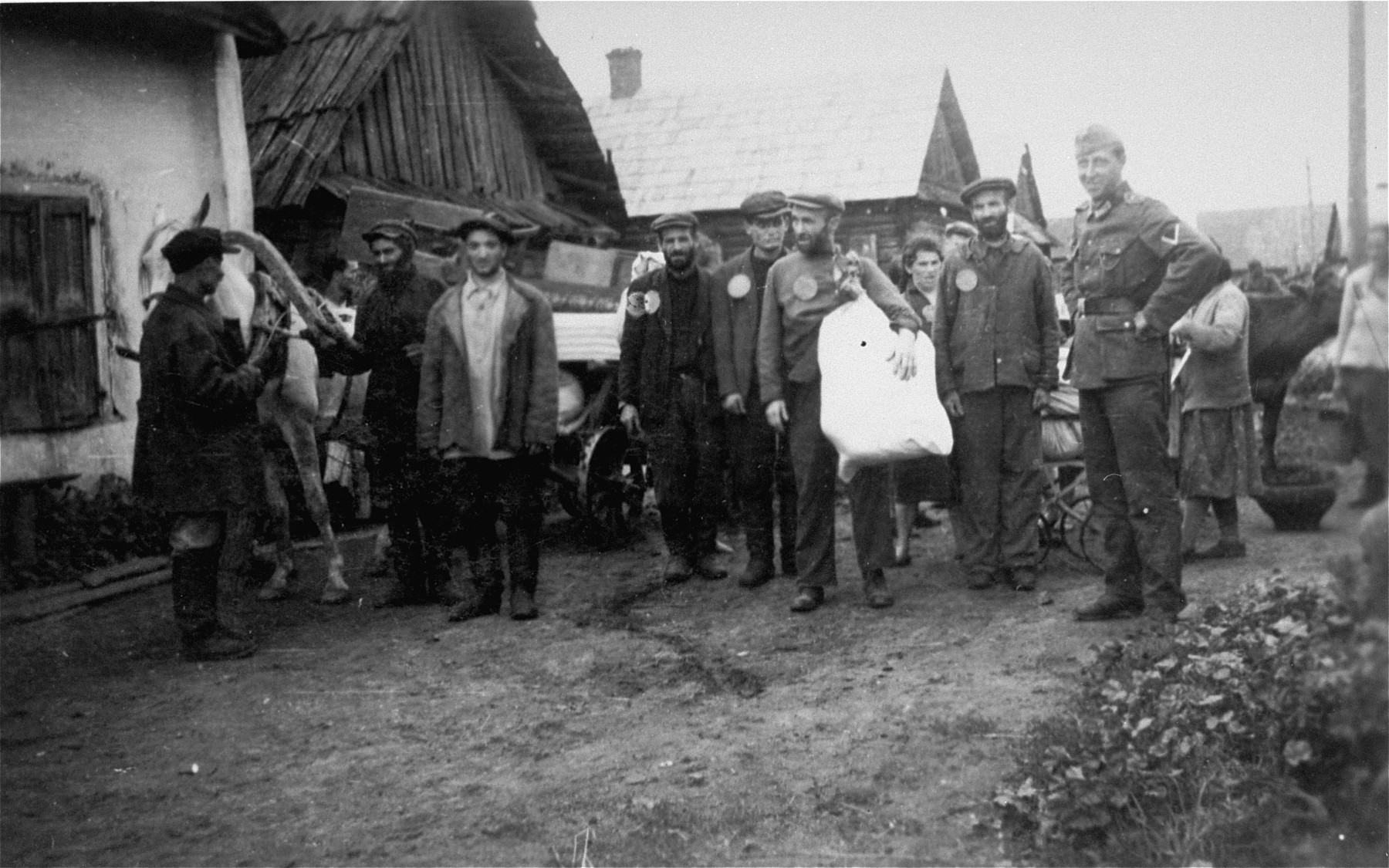 Jews wearing circular badges are gathered with their belongings on an unpaved street during a deportation action from the Krzemieniec ghetto.