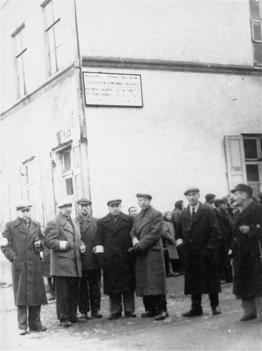 Members of the Jewish council of the Kozienice ghetto stand outside a public kitchen operated by the Jewish community.   Pictured from right to left are: Shmuel Weinberg, Abraham Shabason, Moshe Bronstein (chairman), unknown, Pinchas Freilich, Zygmunt Halputer and Josef Lichtenstein.  In the background, Jews stand in line for food.
