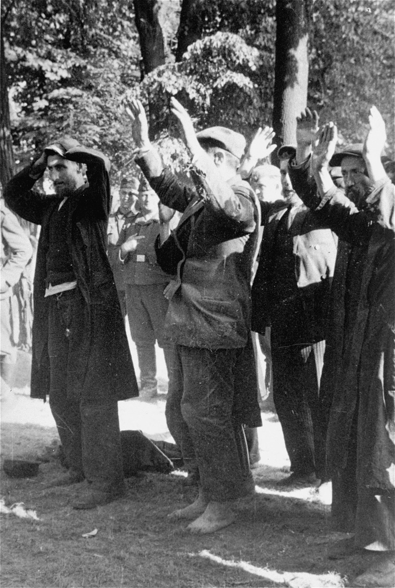 Jews rounded-up in Konskie wait to dig a grave for the bodies of four German soldiers.