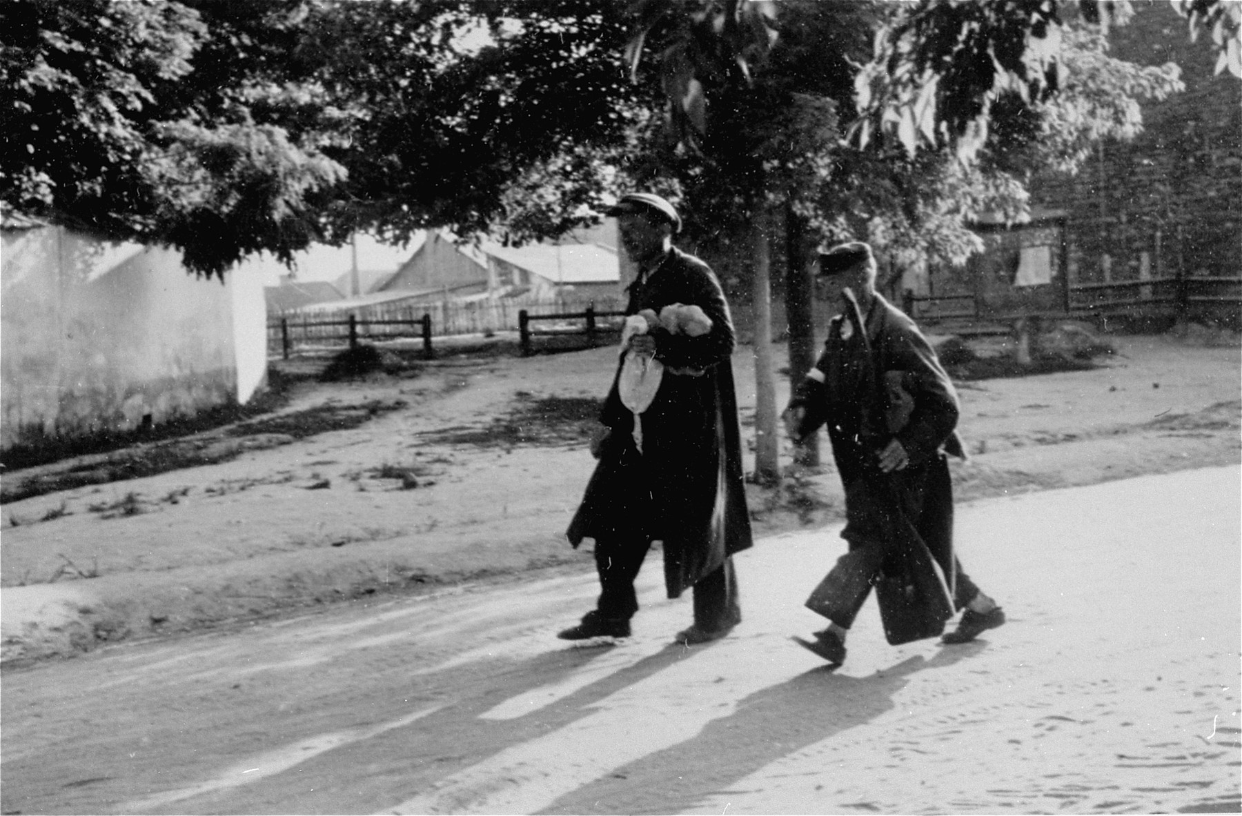 Two Jewish men who have been conscripted for forced labor, walk along an unpaved road in Konskowola.  One of them carries a shovel.