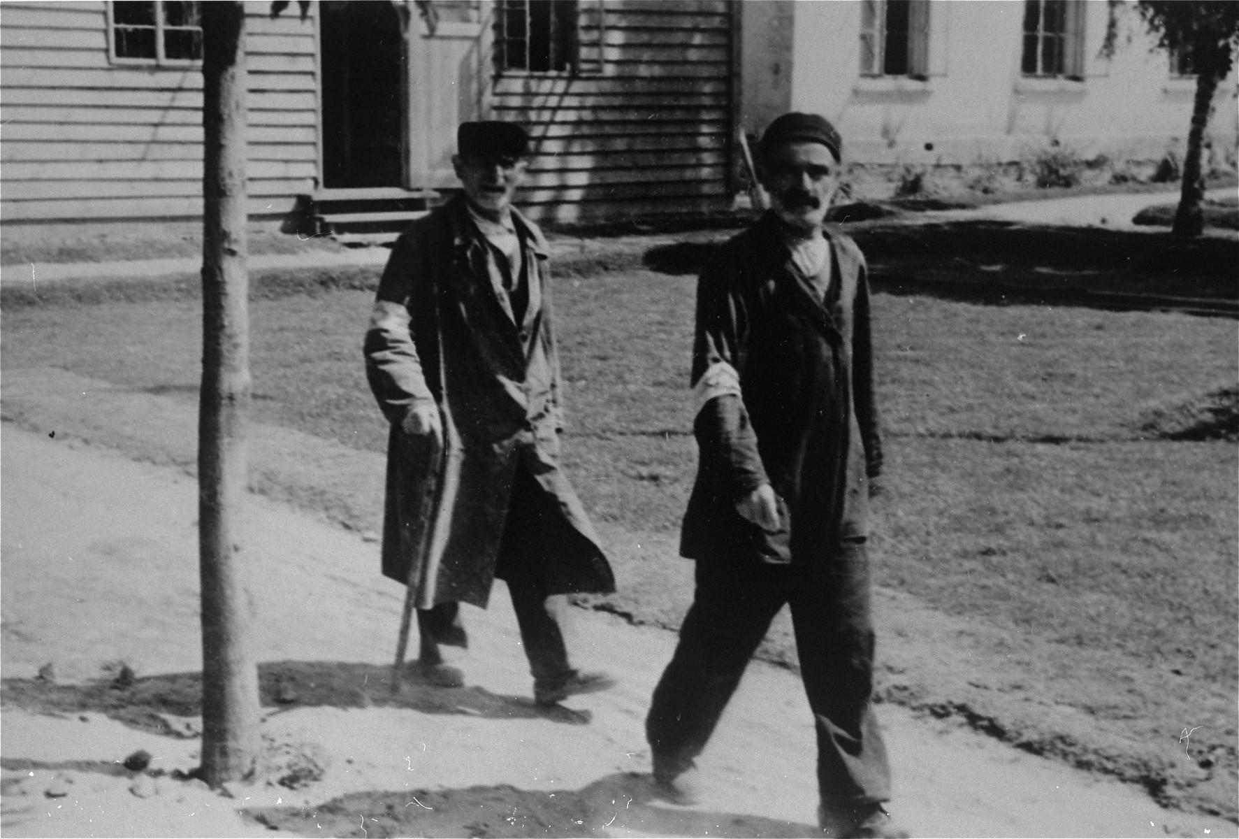 Two Jewish men wearing armbands walk along a path in Konskowola.