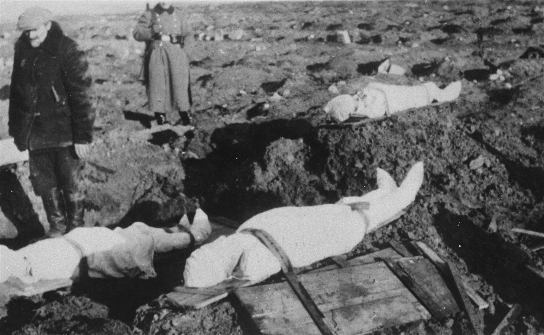 A German soldier stands guard as bodies are prepared for burial at the Jewish cemetery in Kutno.