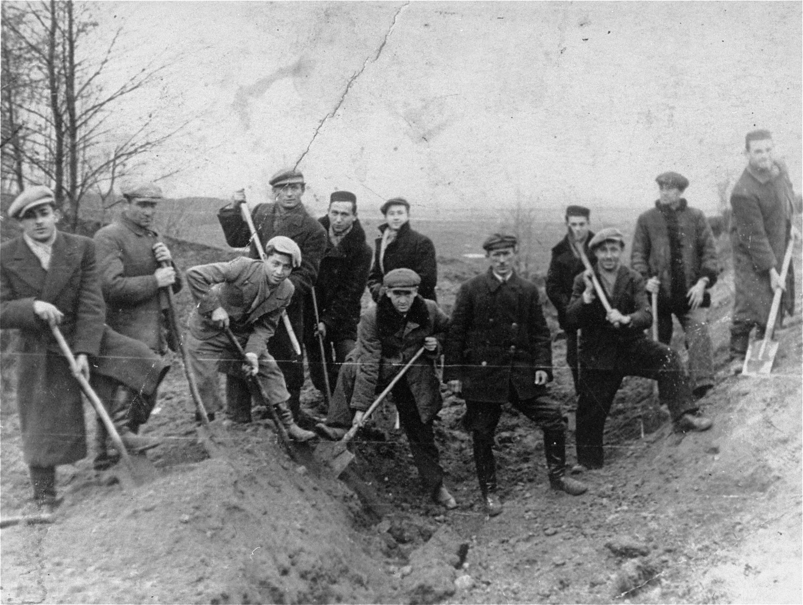Jewish men from the Kozienice ghetto drain a swamp in the nearby village of Wolka.  Among those pictured is Mendel Sirota (far left).   Dovid Silberberg (fourth from left).  Standing in the middle back is David Bayer.  In the front center is Bezalel Berneman.  The Polish man in the middle without a shovel was the supervisor, Rembalski.  On the far right is Scwarzberg.