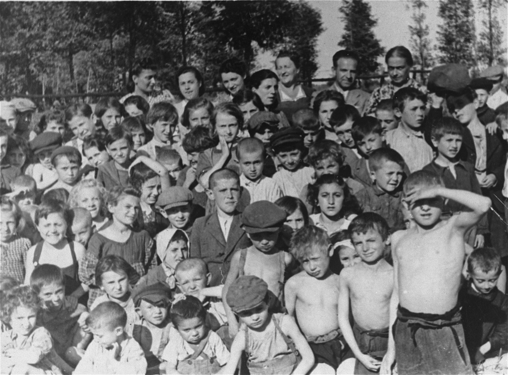 "Group portrait of the staff and children of the ""Kropla Mleka"" welfare organization, which was devoted to feeding hungry children in the Kozienice ghetto."