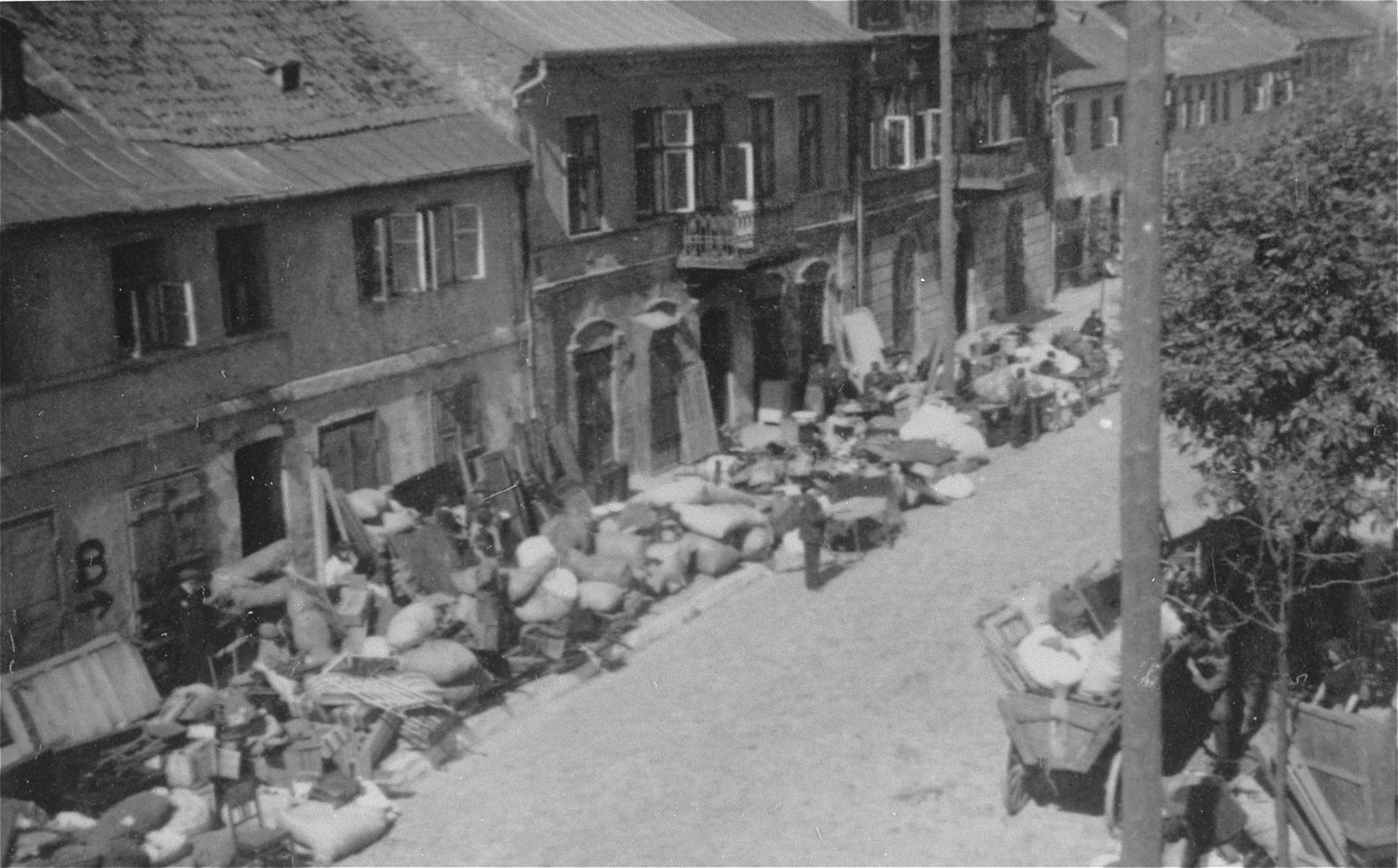 "Piles of furniture and household belongings of Jews who are being transferred to the ghetto cover the pavement of a street in Kutno.  The original German caption reads: ""Evacuation of Kutno. Jews out!"""
