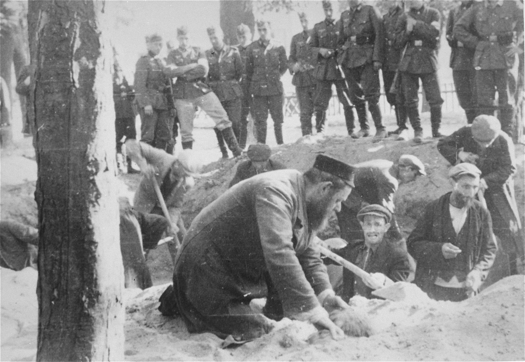 German troops look on as Jews dig a grave for the bodies of four German soldiers that were found in Konskie.