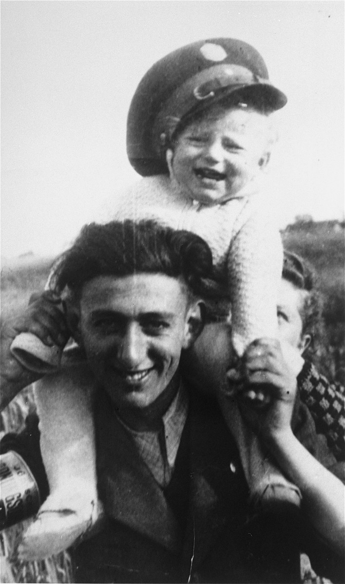 A Jewish policeman in the Minsk Mazowiecki ghetto carries his young cousin, Guta Tyrangiel, on his shoulders.  Guta wears his policeman's hat.