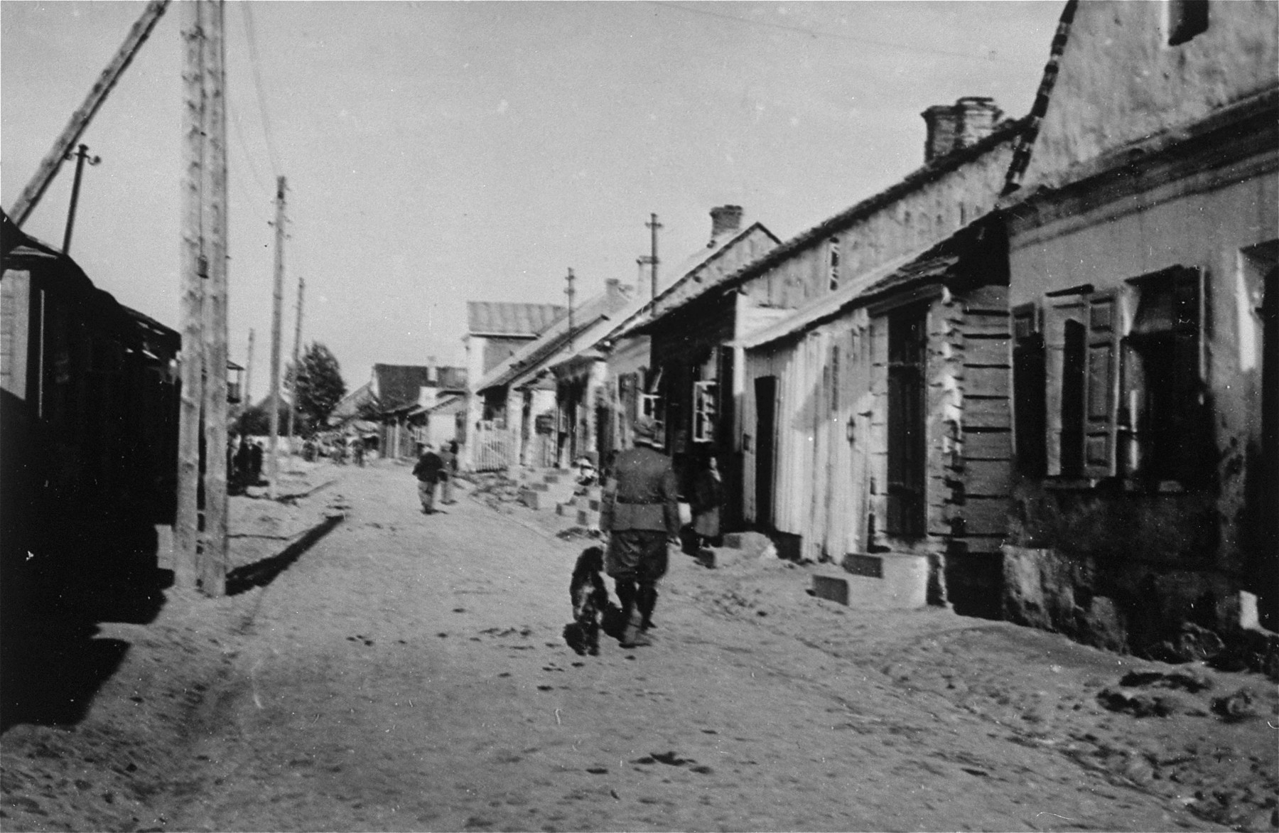 A German soldier patrols a street in the Konskowola ghetto with his dog.