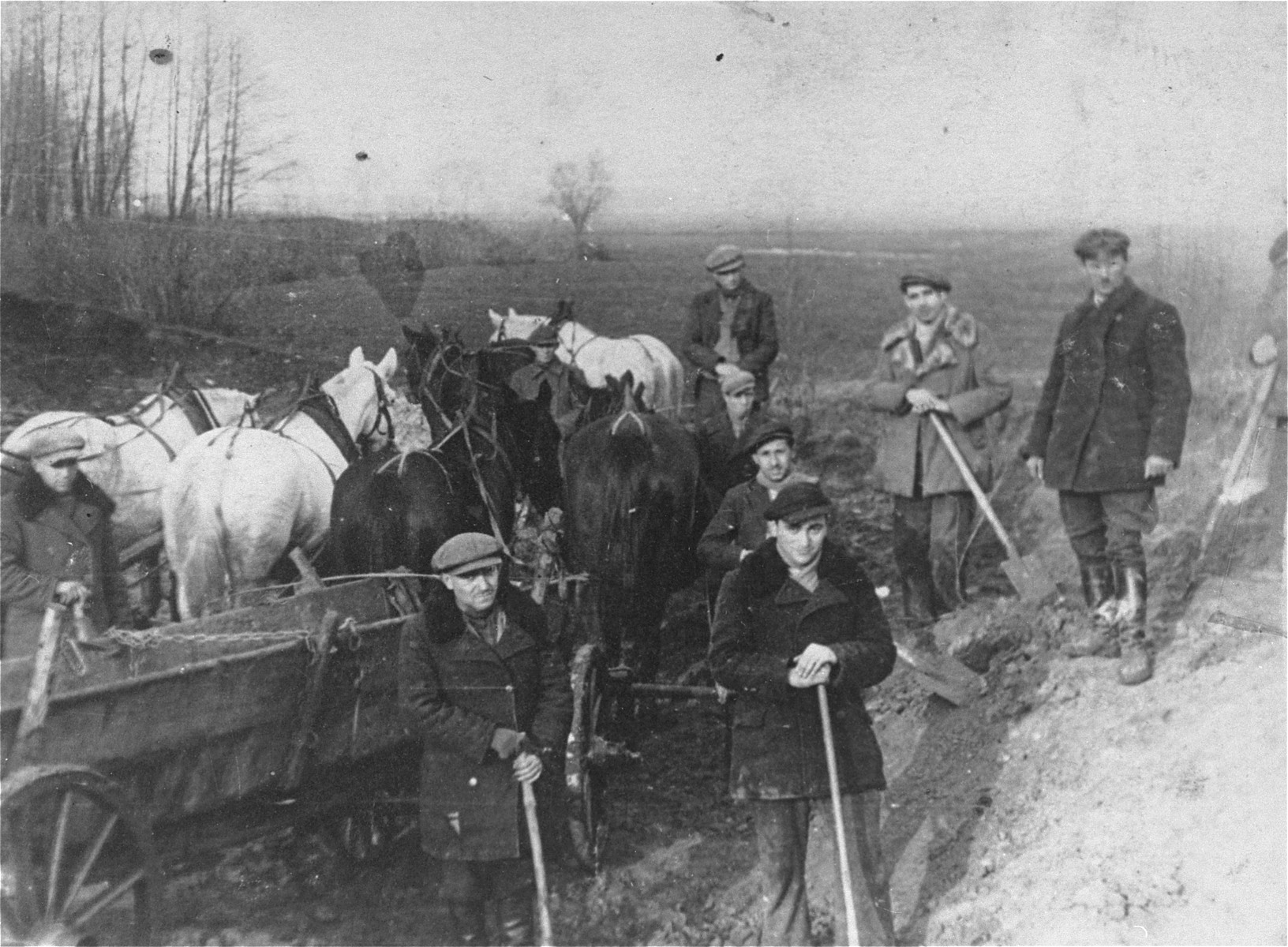 Jewish men from the Kozienice ghetto at forced labor draining a swamp in the nearby village of Wolka.  They are working for the Gorczycki firm who was building a canal.  Pictured on the far right is the Polish supervisor Rembalski.