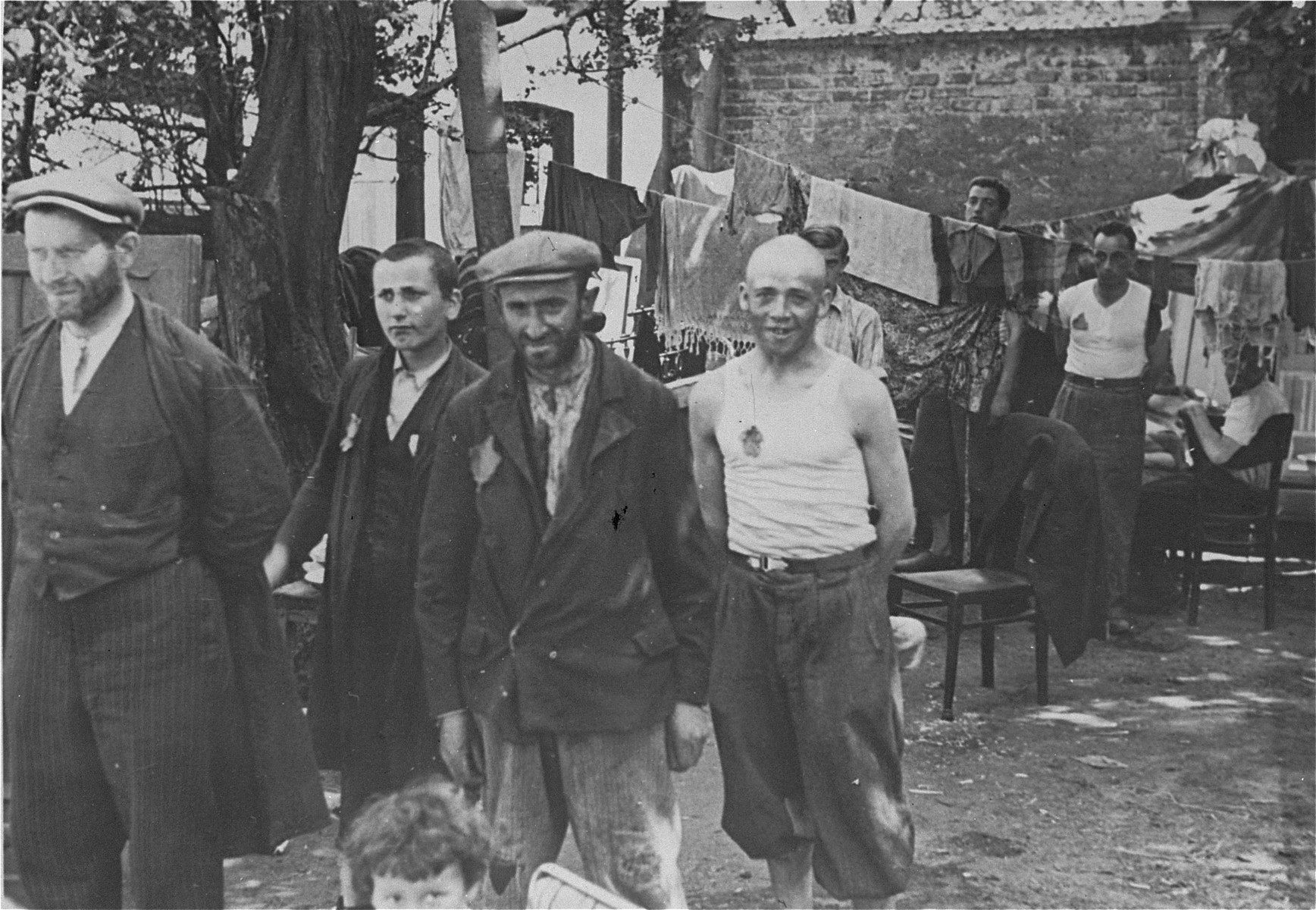 A group of Jewish men stand among furniture and hanging laundry in the Kutno ghetto.