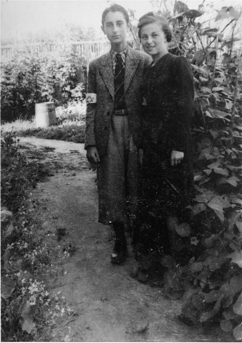 Two Jewish teenagers wearing armbands pose outside in the Konskie ghetto.  Pictured are Herman Neudorf and a friend named Jadzia.