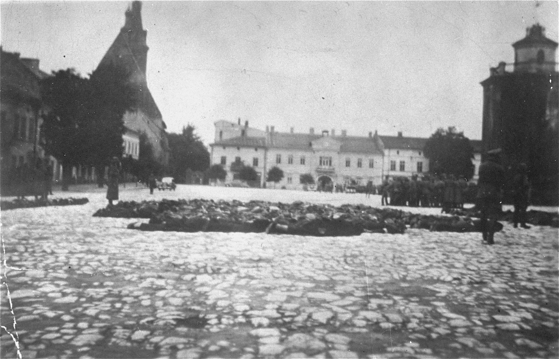 German police stand guard over Jewish hostages assembled on the old market square of Olkusz during a reprisal action.