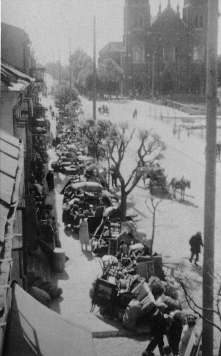 "View of a street in Kutno lined with the belongings of Jews who are being transferred to the ghetto.  The original German caption reads: ""Jews out!"""