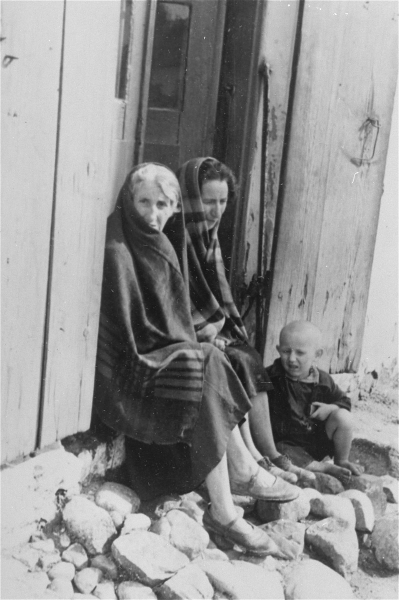 Two Jewish women and a child sit in the doorway of a wooden house in Konskowola.