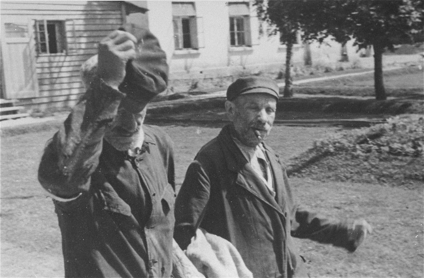 An elderly Jewish man doffs his hat as he walks outside with a companion in Konskowola.