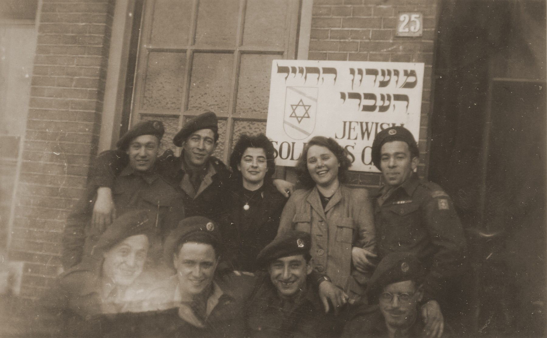 Group portrait of members of the Jewish Brigade in front of the Jewish soldiers' club in Eindhoven, Holland.  Among those pictured is Hersh Makowski  (front center).