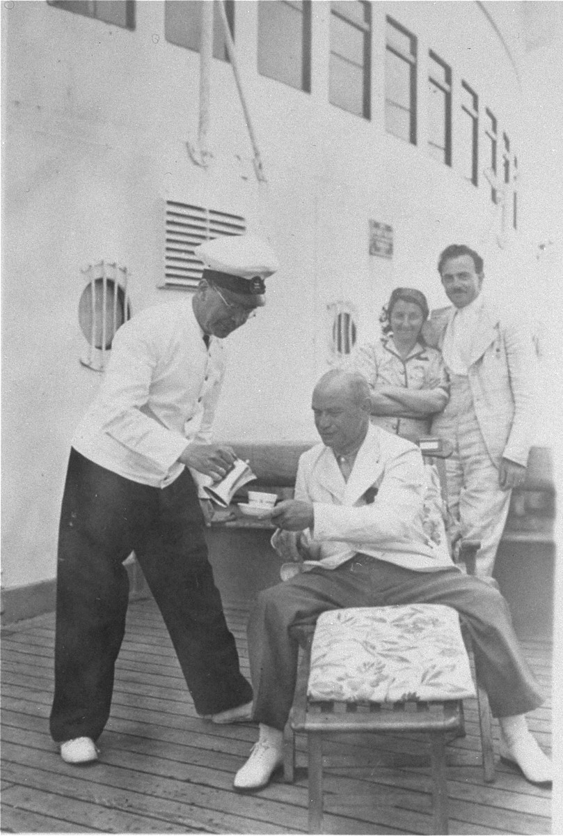 Steward serves coffee to Julius Hermanns on the deck of the MS St.  Louis.     From a photo album belonging to St. Louis passenger Moritz Schoenberger.