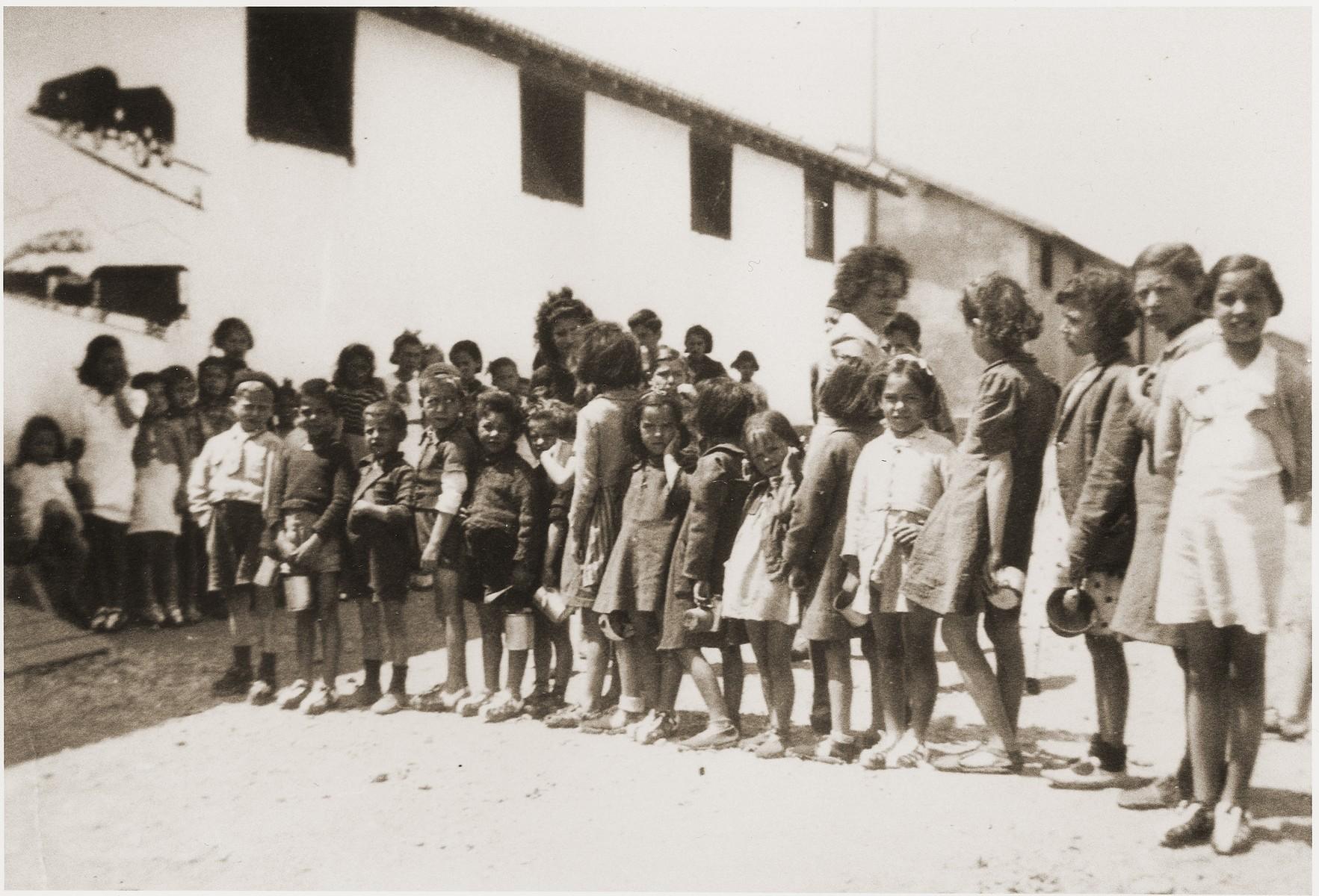 Children wait for a meal at the Secours Suisse barracks.