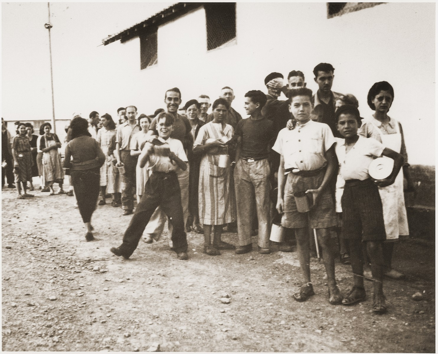 Children wait outside the Secours Suisse barracks for a meal to be served.