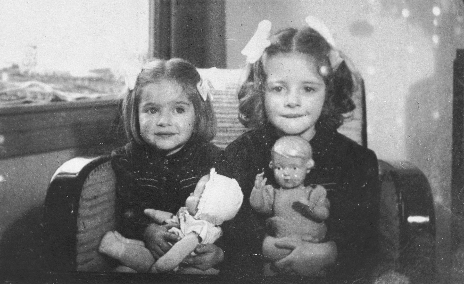 Two Jewish sisters pose with their dolls in their home in The Hague.  Pictured are Eva (right) and Leana (left) Münzer.  Both later perished in Auschwitz.