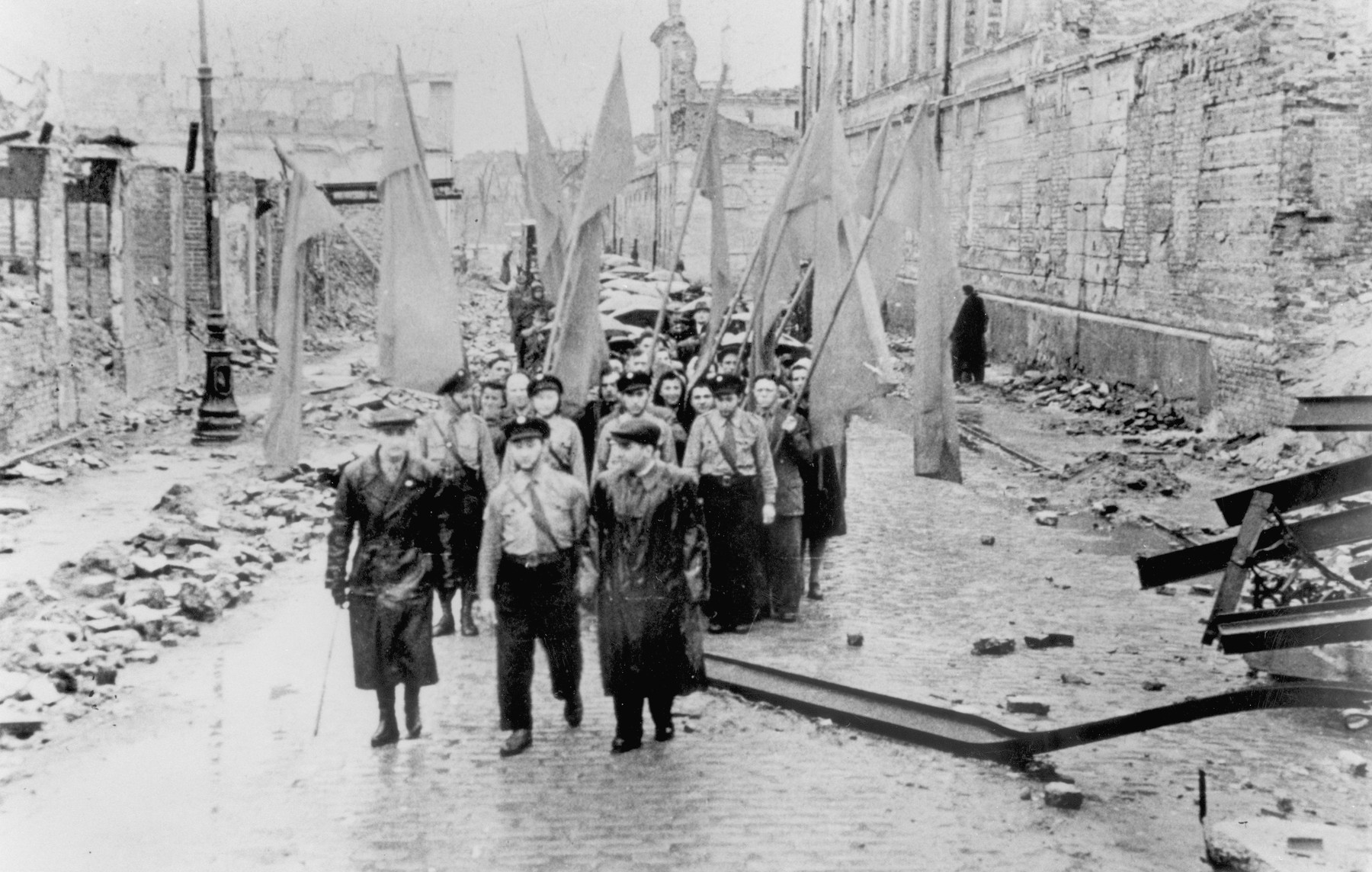 Jewish survivors carrying flags march along Bielanska Street [probably during a demonstration marking the fourth anniversary of the Warsaw ghetto uprising].   The marchers are probably members of the Betar revisionist Zionist movement.