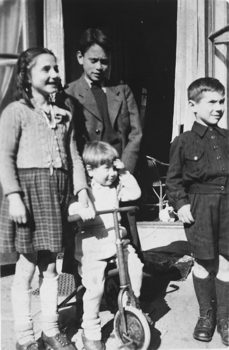 Alfred Münzer, a Jewish child who is living in hiding, poses with his foster brother and two neighbors.  Among those pictured are: Alfred Münzer (on the tricycle) and Robby Madna (the son of rescuer Tolé Madna, behind Alfred).