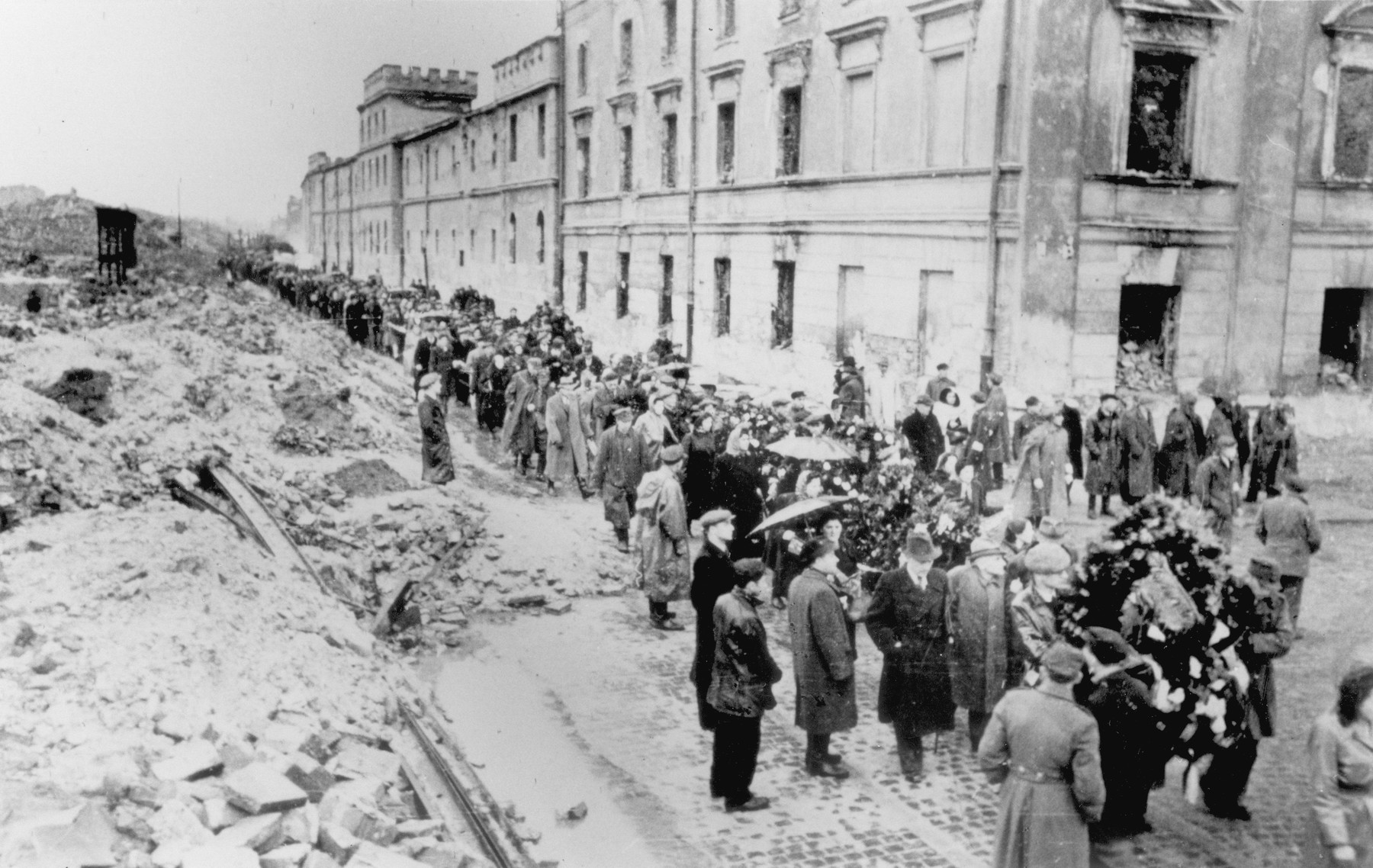 Jewish survivors carrying flags march through the ruins of the Warsaw ghetto [probably during a demonstration marking the fourth anniversary of the Warsaw ghetto uprising].