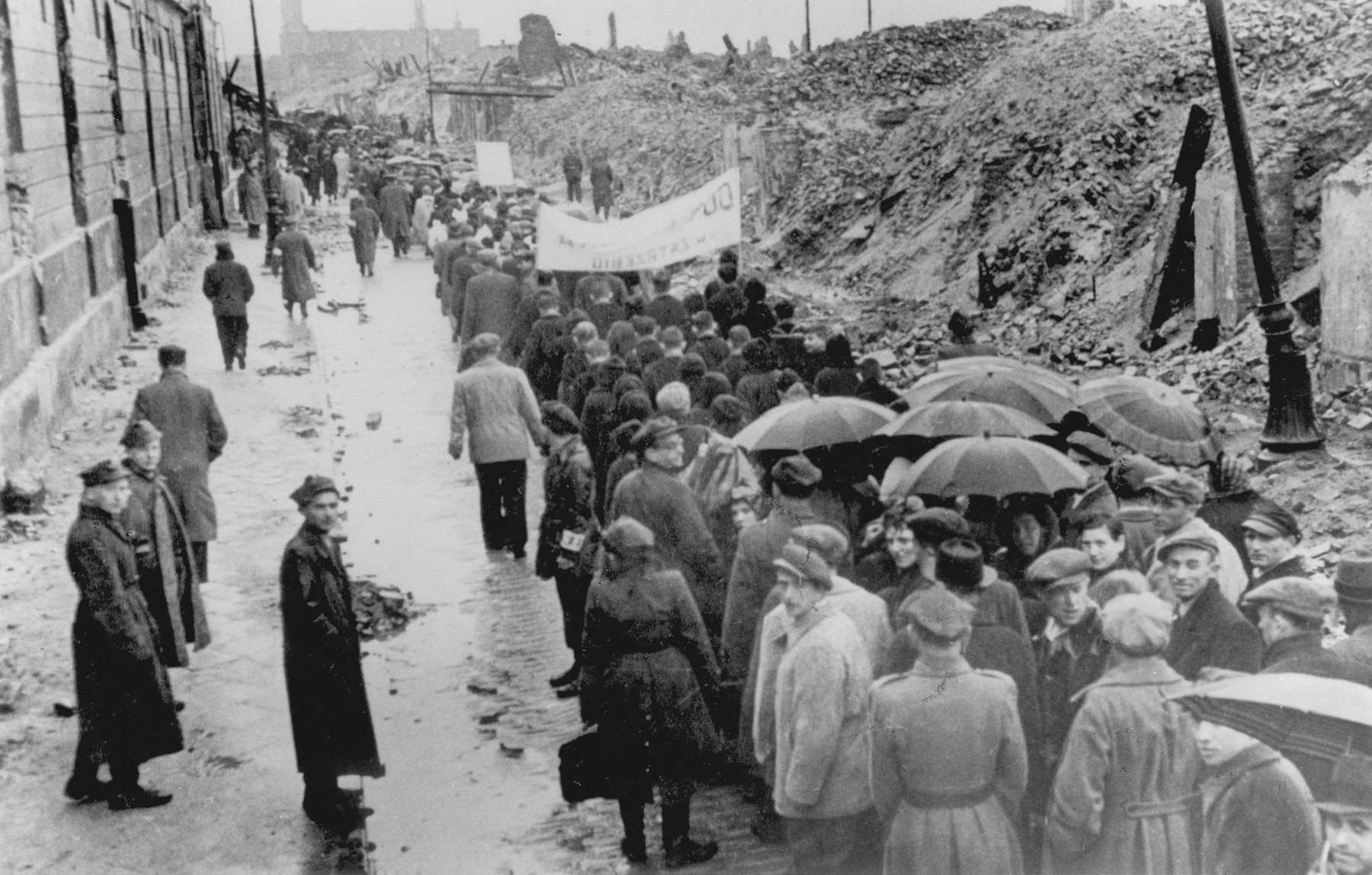 A group of Jewish survivors marches through the ruins of the Warsaw ghetto during a demonstration [probably to mark the fourth anniversary of the Warsaw ghetto uprising].