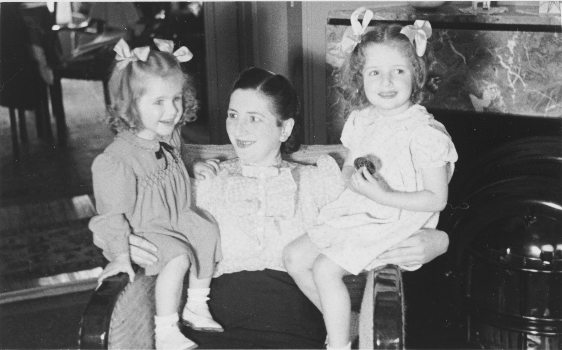 Gitel Münzer sits on an armchair with her two daughters, Eva (right) and Leana (left).  The two children later perished in Auschwitz.