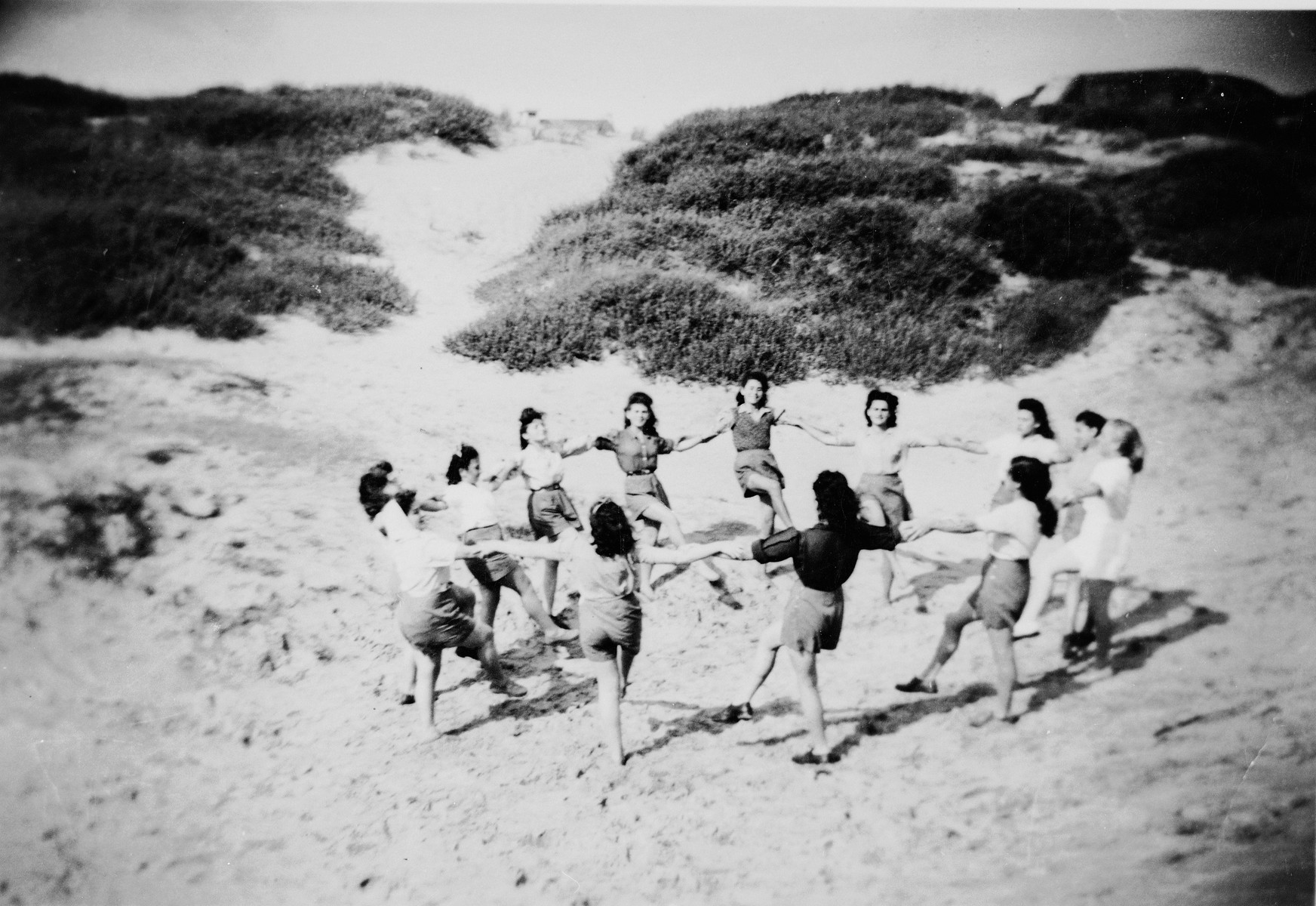 Children who had been in hiding during the war dance a hora on a beach.