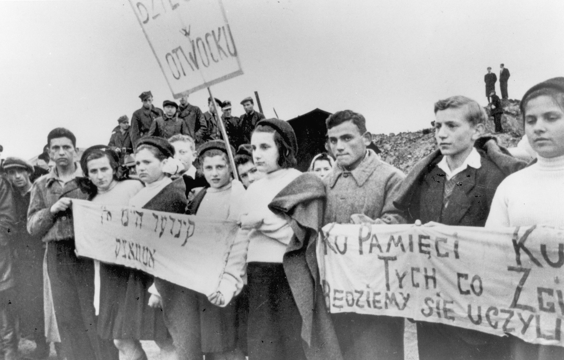 Jewish children from Otwock carrying signs and banners attend a demonstration [probably to mark the fourth anniversary of the Warsaw ghetto uprising].