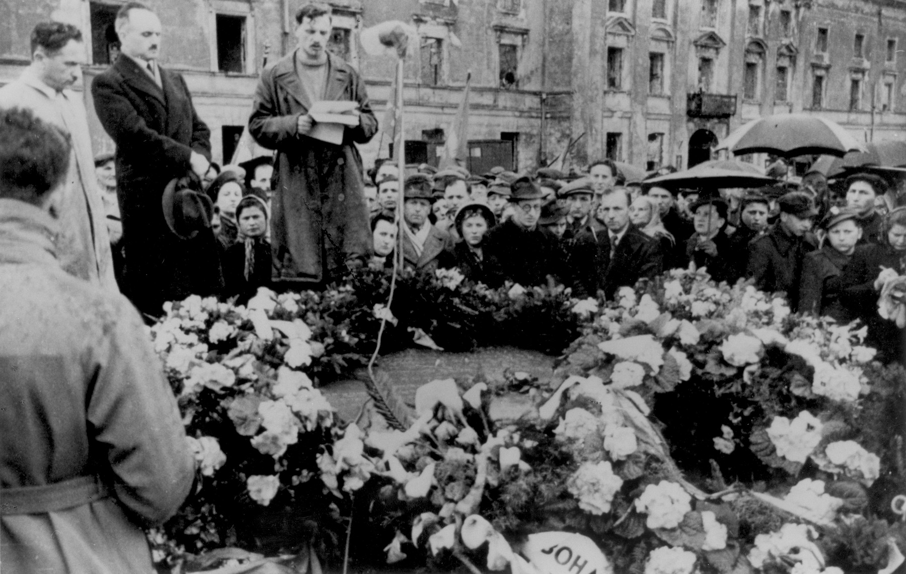 Yitzhak Zuckerman delivers a speech at a ceremony in front of the ruins of the former headquarters of the Warsaw ghetto Jewish council [probably to mark the fourth anniversary of the Warsaw ghetto uprising].  Also pictured is Dr. Adolf Berman (standing next to Zuckerman).