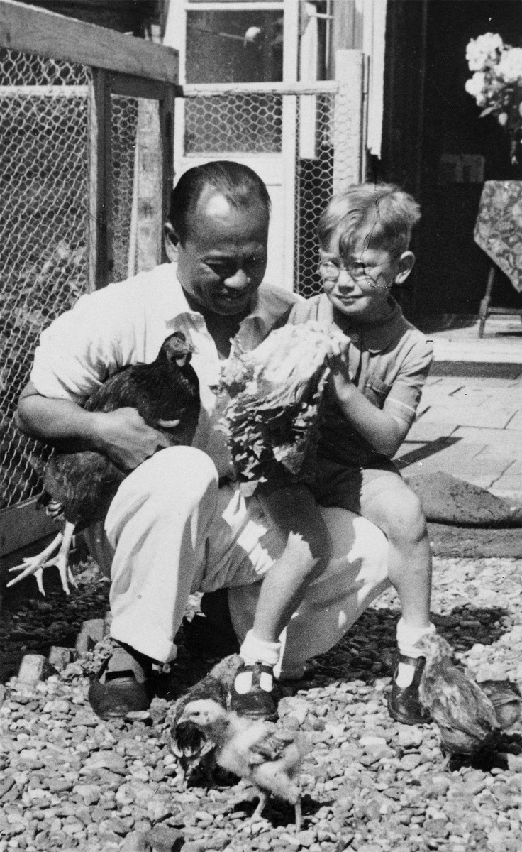 A Jewish child and his Indonesian-Dutch rescuer sit outside holding chickens during a postwar visit.  Pictured are Alfred Münzer and Tolé Madna.