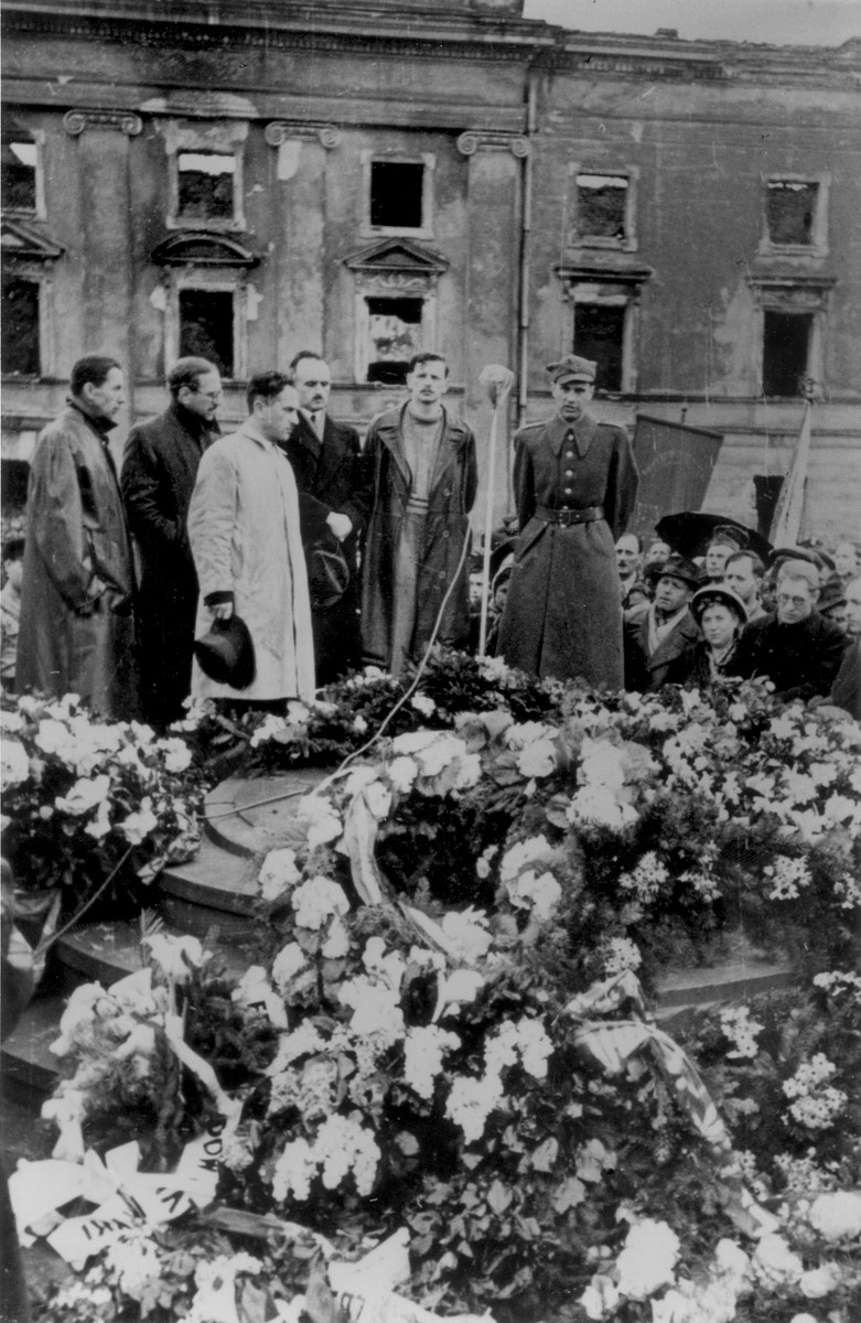 Jewish leaders conduct a ceremony in front of the ruins of the former headquarters of the Warsaw ghetto Jewish council [probably to mark the fourth anniversary of the Warsaw ghetto uprising].  Among those pictured are Dr. Adolf Berman (third from the right) and Yitzhak Zuckerman (second from the right).