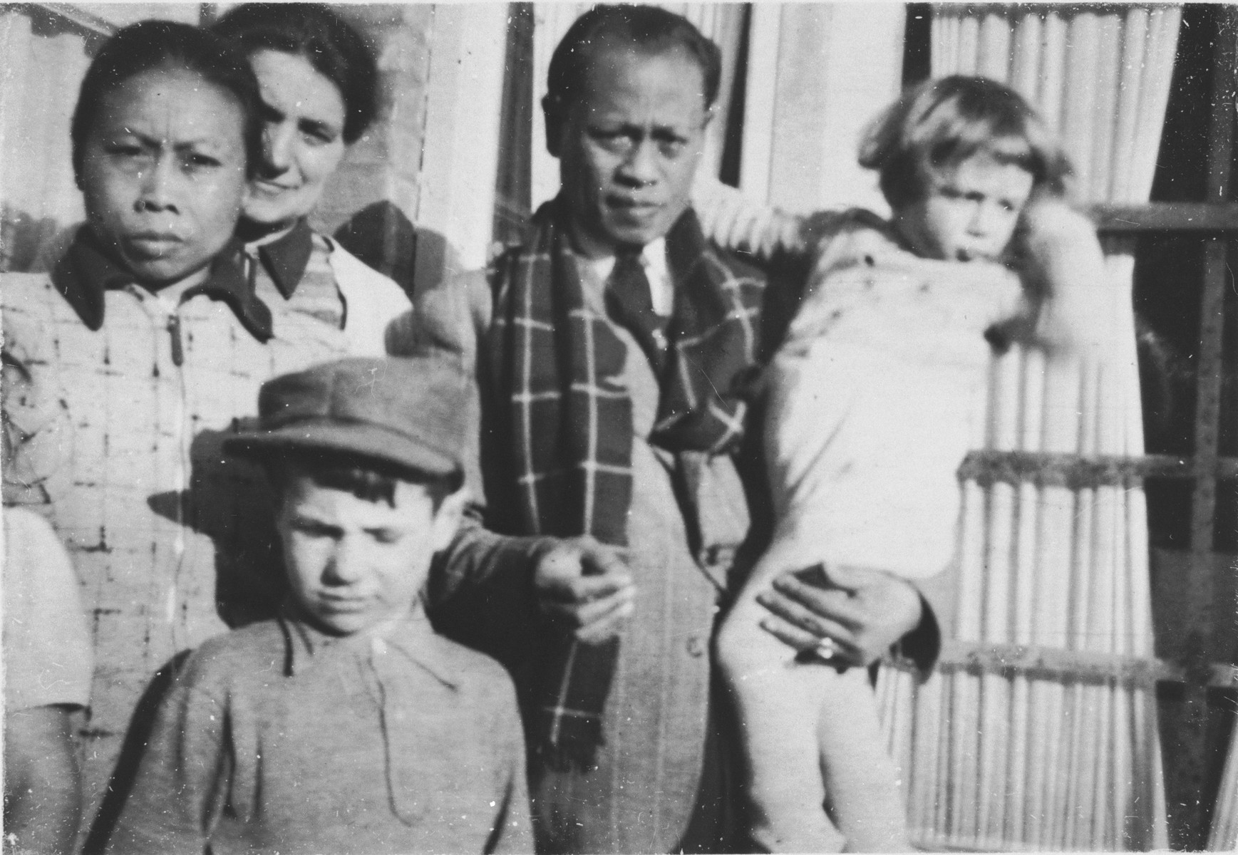 Indonesian-Dutch rescuers pose with the Jewish child they are hiding in The Hague.  Among those pictured are Alfred Münzer (right), Tolé Madna (center, holding Alfred) and Mima Saïna (left).