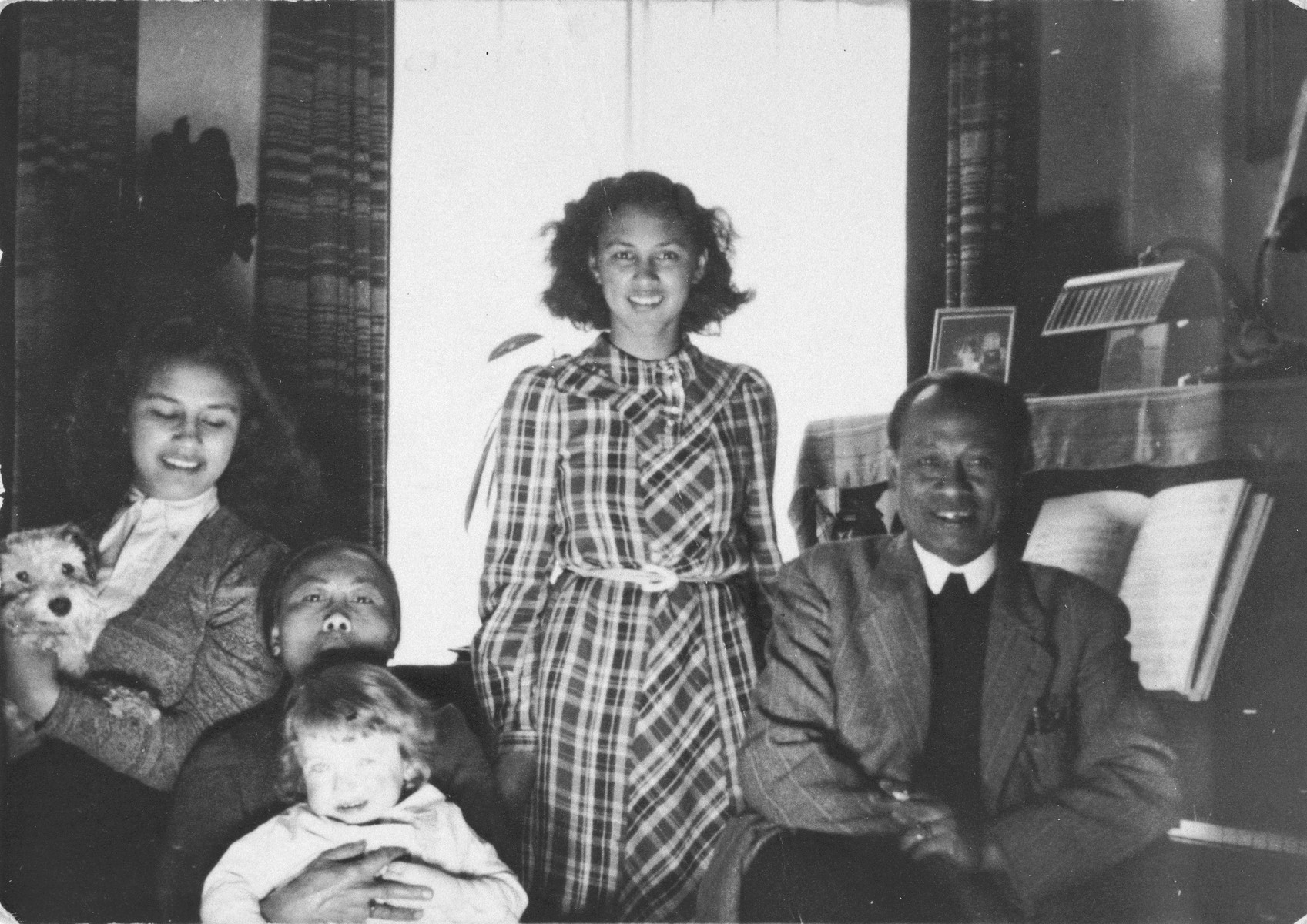 Members of the Madna household pose with the Jewish child they are hiding in their home in The Hague.  Pictured clockwise from the bottom left are: Alfred Münzer (child), Mima Saïna (nanny), Willie Madna (daughter of rescuer, Tolé Madna), Dewie Madna (daughter of Tolé Madna) and Tolé Madna.