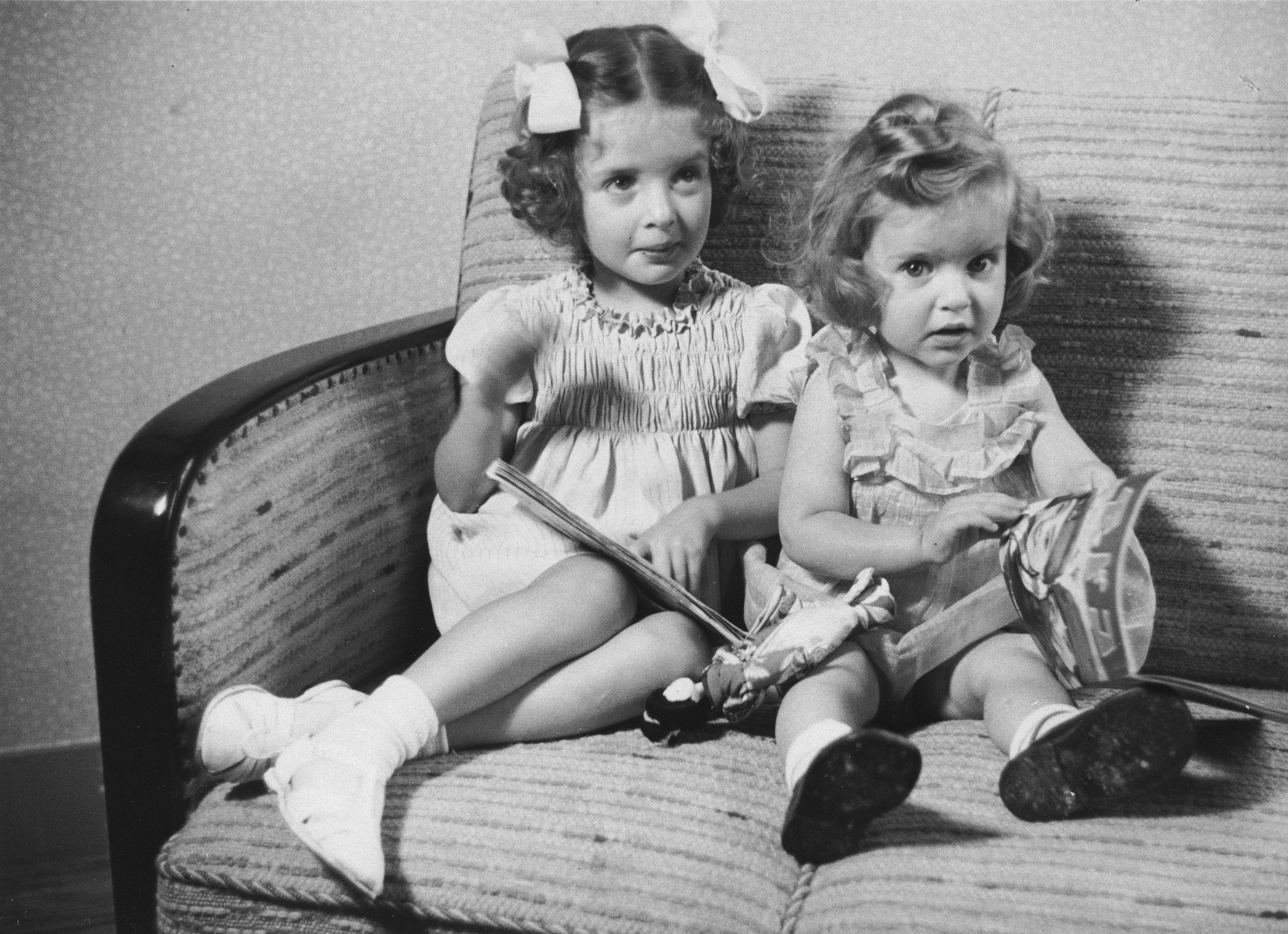 Two Jewish sisters, Eva and Leana Münzer, sit on a sofa in their home in The Hague.